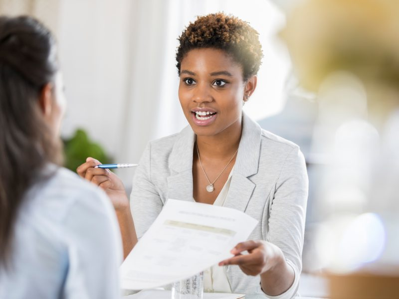 Young businesswoman has a serious expression on her face while discussing a document with a female colleague.